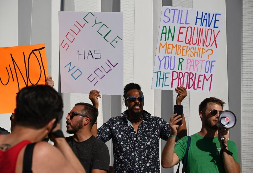Protesters chant slogans and hold signs outside the luxury gym Equinox in West Hollywood, California, August 9, 2019, during a protest against the gym and fitness company SoulCycle as well as against President Trump and his benefactor Stephen Ross., who hosted a high-dollar fundraising event for Trump.