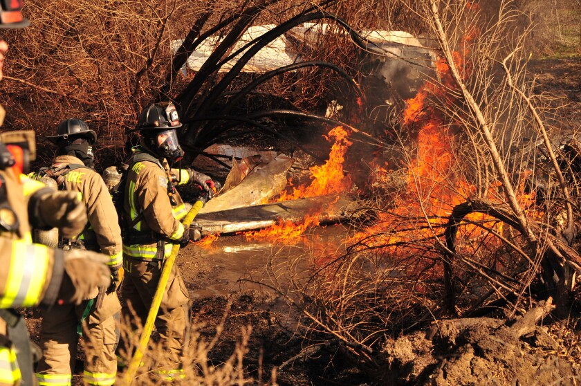 Firefighters working against a firey plane crash amid brush.