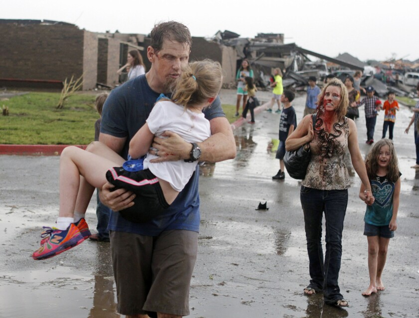 Teachers carry children away from Briarwood Elementary after a tornado destroyed the school in south Oklahoma City on May 20, 2013. Officials are now debating how to pay for putting storm shelters in public schools.