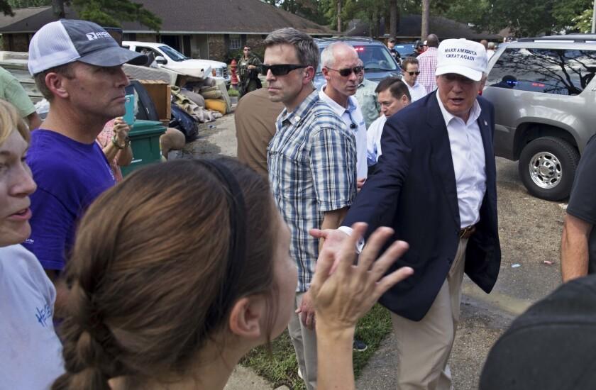 El candidato presidencial republicano Donald Trump saluda a víctimas de las inundaciones durante un recorrido por una zona dañada en Denham Springs, Luisiana, el viernes 19 de agosto de 2016. (AP Foto/Max Becherer)
