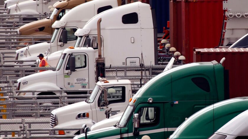 WILMINGTON, CA -- NOVEMBER 1, 2017 -- A driver walks past a row of trucks that prepare to leave the