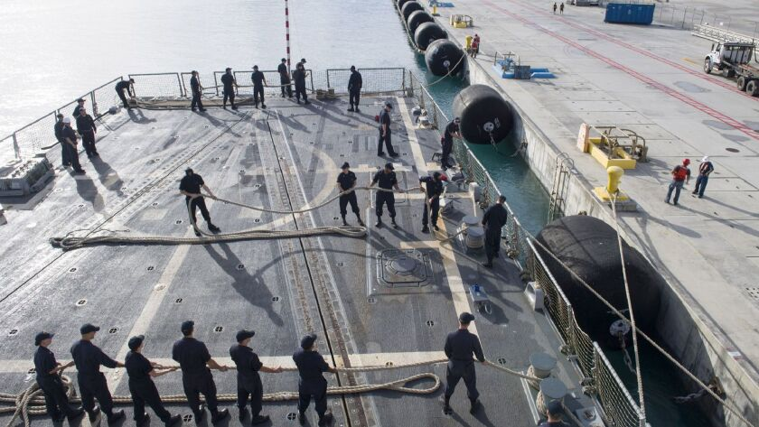 Sailors man their mooring lines aboard the guided-missile destroyer Sterett as the ship departs Nava