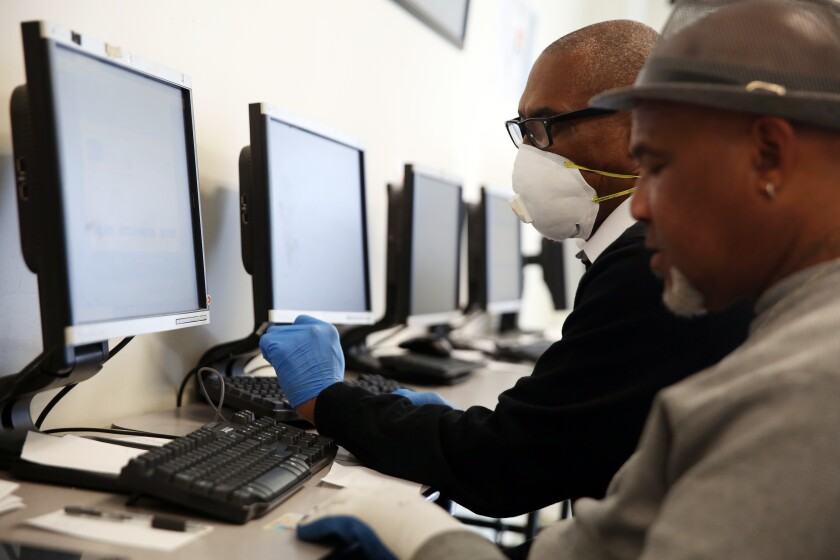 Stanley Smith, left, with South L.A. WorkSource Center, helps Gregory Allen with online job search services.