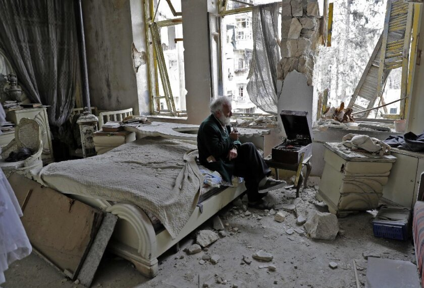 Mohammad Mohiedine Anis, 70, smokes his pipe as he sits in his destroyed bedroom listening to music on his vinyl player in Aleppo's formerly rebel-held al-Shaar neighbourhood.