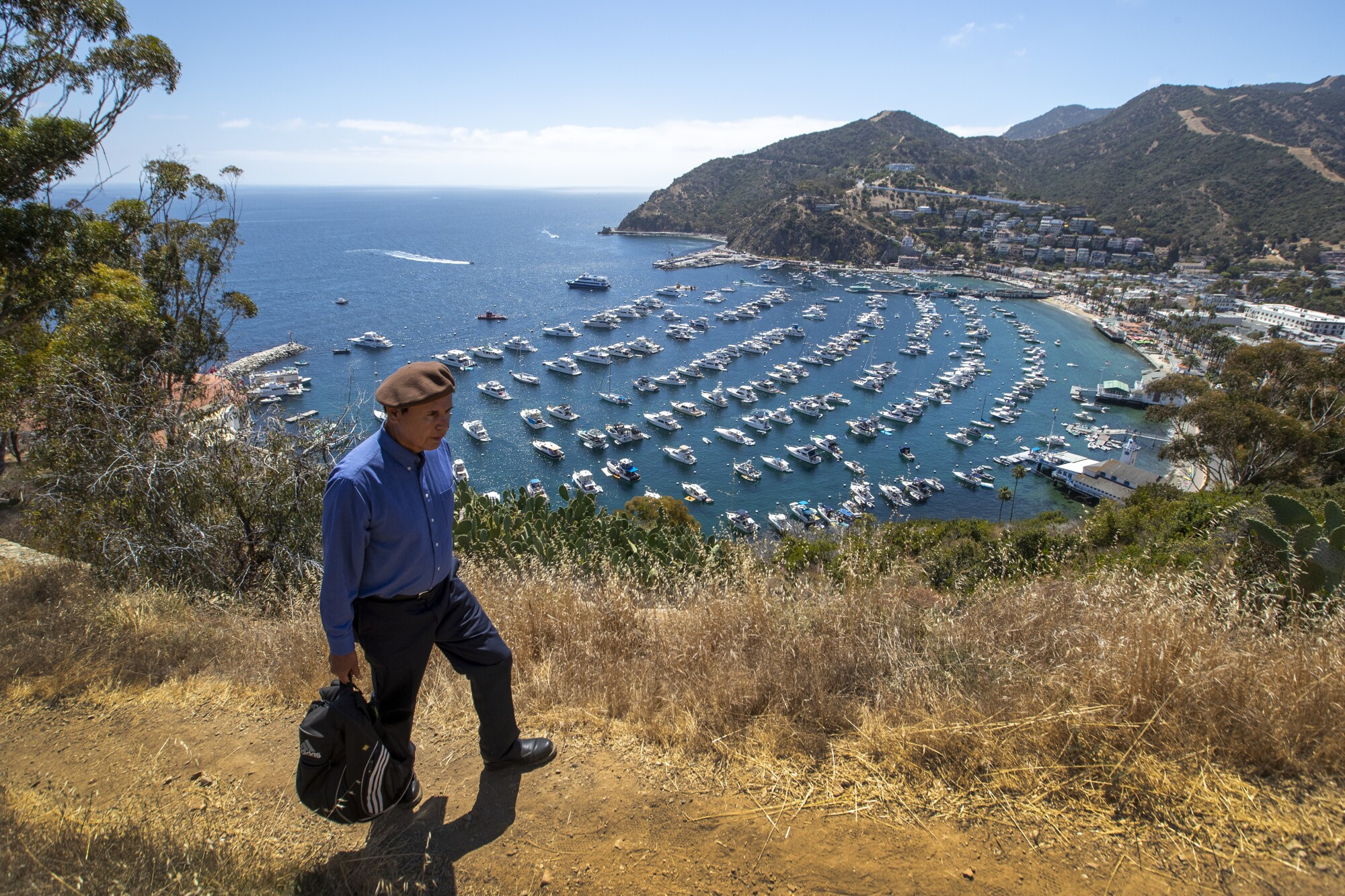 Chicano activist David Sanchez, wearing the signature brown beret, hikes on Catalina Island to the site of 1972 protest camp