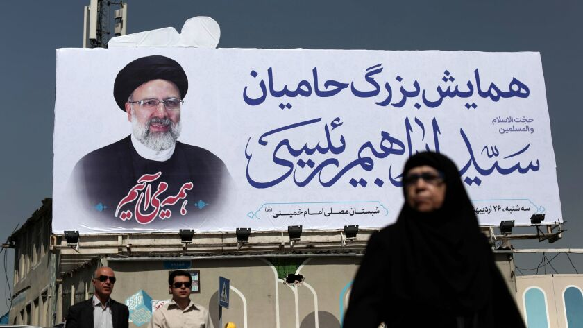 An Iranian woman walks past a portrait of presidential challenger Ebrahim Raisi in Tehran.