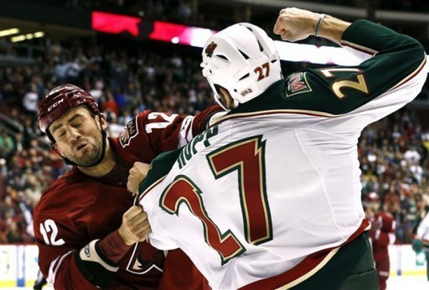 Minnesota Wild's Mike Rupp (27) fights with Phoenix Coyotes' Paul Bissonnette (12) during the first period in an NHL hockey game, Thursday, Feb. 28, 2013, in Glendale, Ariz. (AP Photo/Ross D. Franklin)