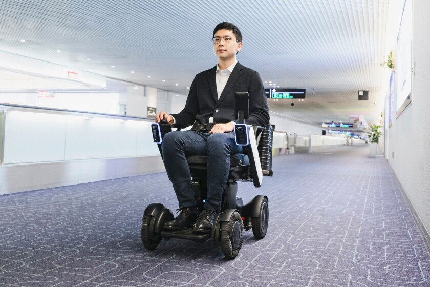 This photo provided by WHILL, Inc., shows the trial of the company's Autonomous Drive System at Haneda Airport in Tokyo in November, 2019. The autonomous mobility system, which works like a wheelchair without anyone pushing it, is scuttling around a Tokyo airport to help with social distancing amid the coronavirus pandemic. (WHILL, Inc. via AP)