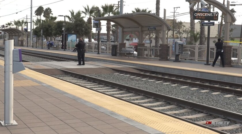 SDPD officers string up crime scene tape Saturday at the Palm Avenue trolley station after a man was stabbed at the site.