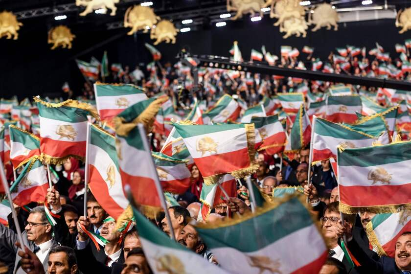 """Mujahedin Khalq members wave Iranian flags during the conference, titled """"120 Years of Struggle of the Iranian People for Freedom,"""" at the Ashraf-3 camp, a base for the Iranian group, in Manza, Albania, on July 13, 2019."""