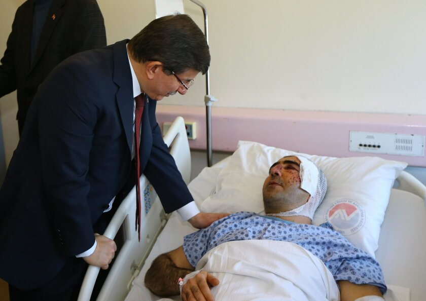 Turkish Prime Minister Ahmet Davutoglu, left, talks to a man, wounded in Wednesday's explosion in Ankara, Turkey, during a visit at the hospital, Thursday, Feb. 18, 2016. The explosion occurred during evening rush hour in the heart of Ankara, in an area close to parliament and armed forces headquar