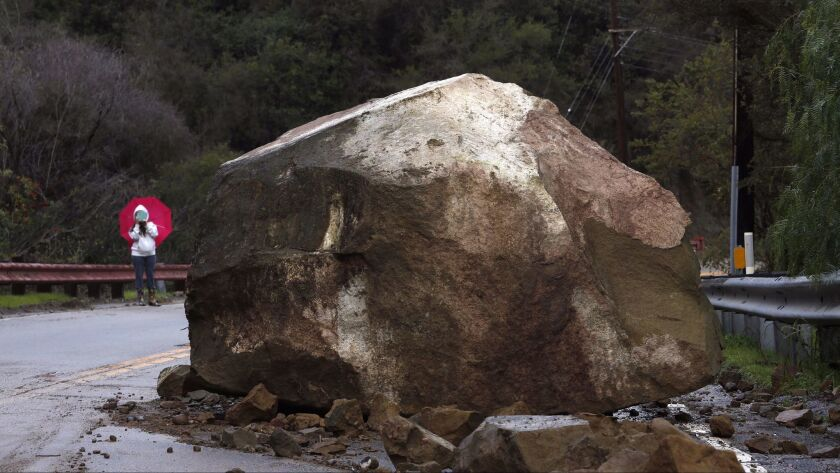 Gina Picciolo takes a picture of a boulder that fell onto Topanga Canyon Boulevard in January.