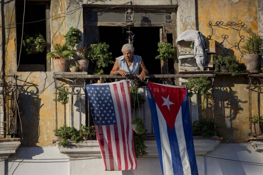 Javier Yanez stands on his balcony decorated with U.S. and Cuban flags in Old Havana on Dec. 19, 2014. If all travel restrictions were lifted, round-trip flights from the U.S. to Cuba would drop in price by an average of 50%, according to a new study.