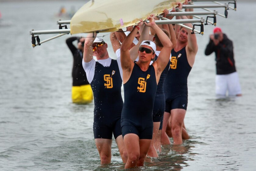 In a photo from the 2013 Crew Classic, UCSD men's crew carries their boat from the water after racing.