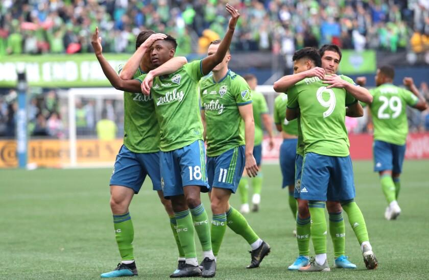 Seattle's Kelvin Leerdam (18) celebrates with teammates after scoring a goal.