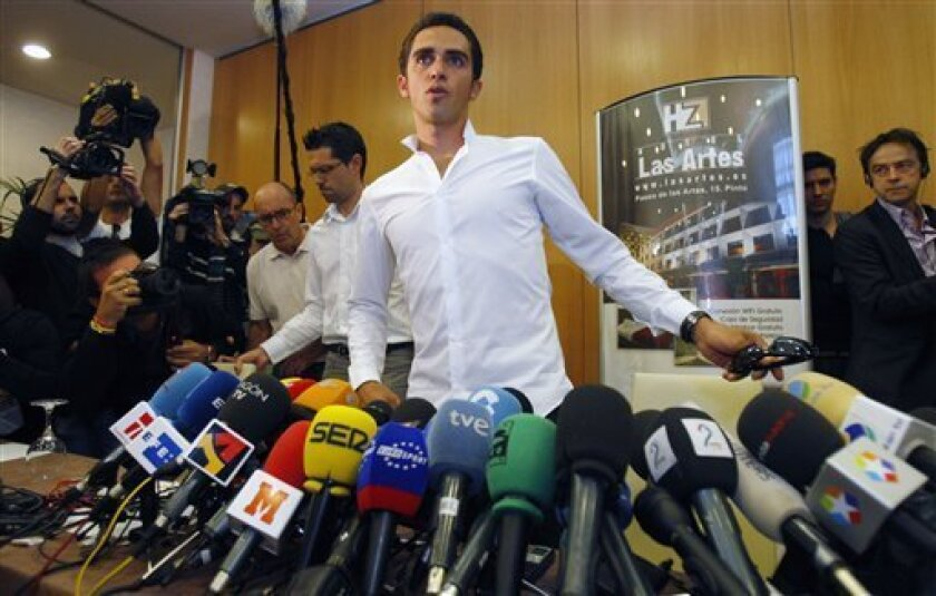 Cyclist Alberto Contador of Spain takes his seat to give a press conference in Pinto on the outskirts of Madrid, Thursday Sept. 30, 2010. Three-time Tour de France champion Alberto Contador tested positive for a banned drug while winning this year's race and has been suspended by cycling's governing body. (AP Photo/Andres Kudacki)