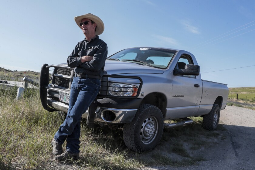 A man in a cowboy hat leans against a truck