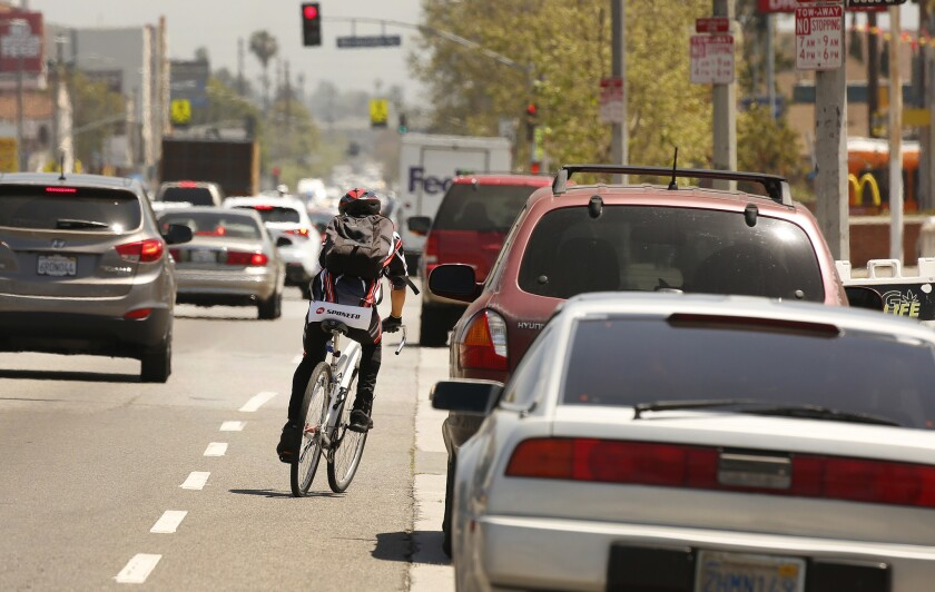 A cyclist rides next to a lane of parked cars on Manchester Avenue in South Los Angeles, one of the deadliest streets in the city for pedestrians and cyclists.