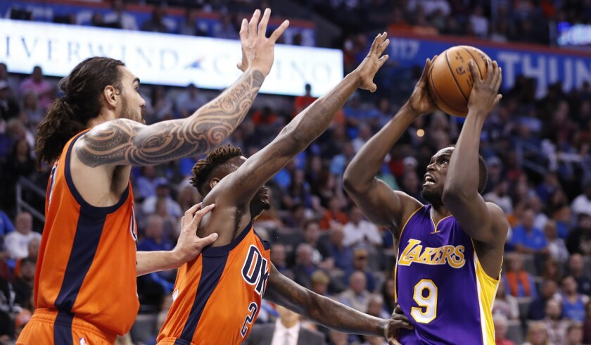Lakers forward Luol Deng shoots as Thunder guard Anthony Morrow (2) and center Steven Adams (12) defend during their Oct. 30 game in Oklahoma City.