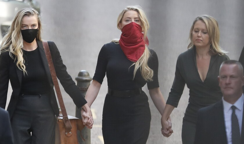 Actress Amber Heard, center, arrives at the High Court in London.