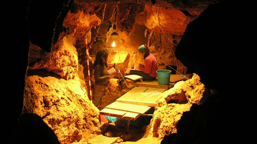 """Researchers work in El Sidrón cave's """"Tunnel of Bones,"""" where 12 Neanderthal specimens have been recovered."""