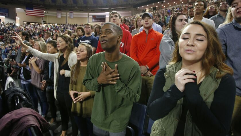 FILE - In this Wednesday, Oct. 12, 2016 file photo, Liberty University students sing and pray prior