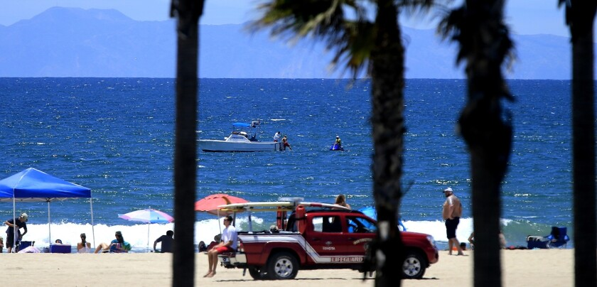 """Lifeguards closed access to water off the coast of Huntington Beach Friday after a shark exhibited """"aggressive behavior"""" and bumped a surfer."""