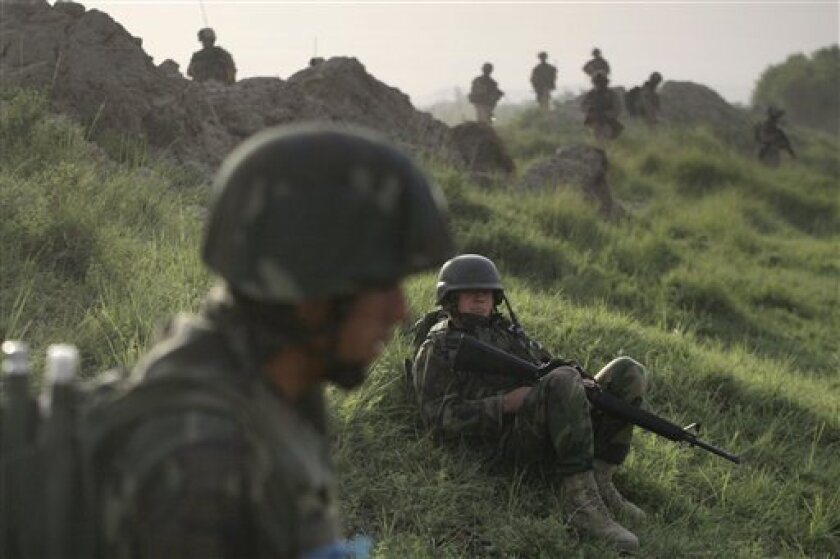 Afghan National Army soldiers and U.S. Marines from the 2nd MEB, 1st Battalion 5th Marines patrol in the Nawa district of Afghanistan's Helmand province Monday July 6, 2009. (AP Photo/David Guttenfelder)