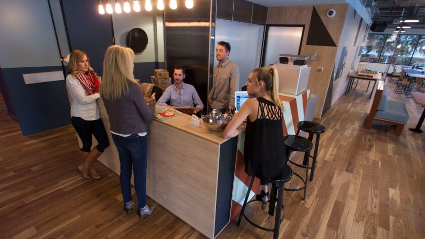 WeWork staff and members gather around the reception desk on the third floor.
