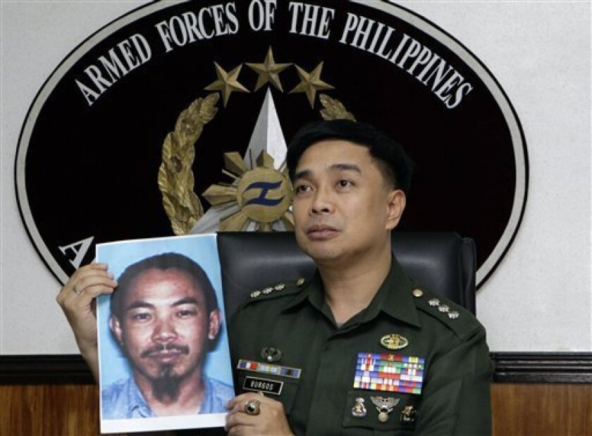 Armed Forces of the Philippines spokesman Col. Marcelo Burgos shows a picture of Malaysian Zulkipli bin Hir, also known as Marwan, a top leader of the regional, al Qaida-linked Jemaah Islamiyah terror network, during a press conference Thursday, Feb. 2, 2012 in suburban Quezon City, north of Manila, Philippines. The military said it killed Southeast Asia's most-wanted terrorist and two other senior militants Thursday in a U.S.-backed airstrike that would mark one of the region's biggest anti-terror successes in recent years. The dead included Zulkipli bin Hir, leader of the Philippines-based Abu Sayyaf militants, Umbra Jumdail, and a Singaporean leader in Jemaah Islamiyah, Abdullah Ali. (AP Photo/Pat Roque)