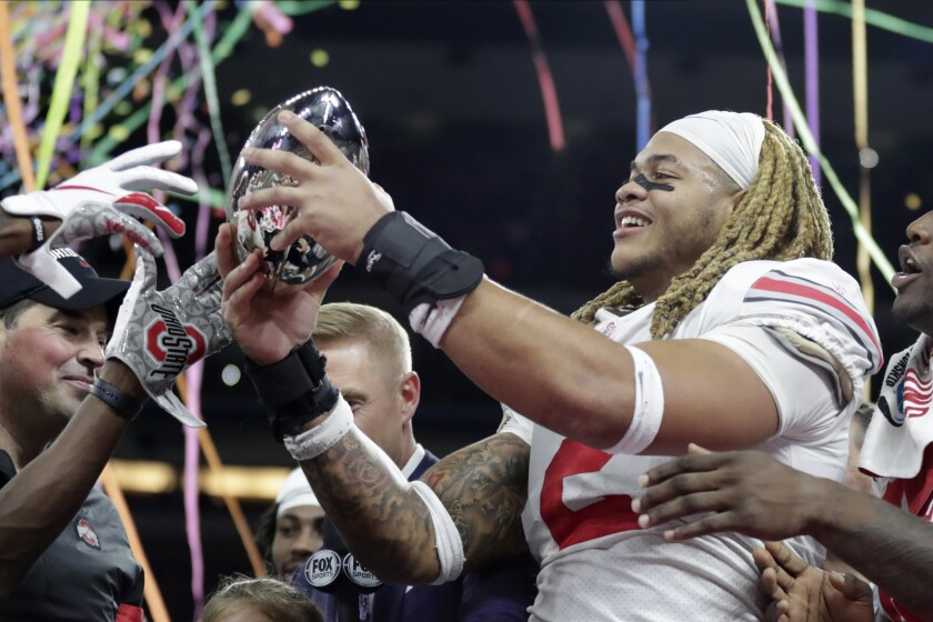 Ohio State defensive end Chase Young (2) holds the trophy following the team's 34-21 win over Wisconsin in the Big Ten championship NCAA college football game, early Sunday, Dec. 8, 2019, in Indianapolis. (AP Photo/Michael Conroy)