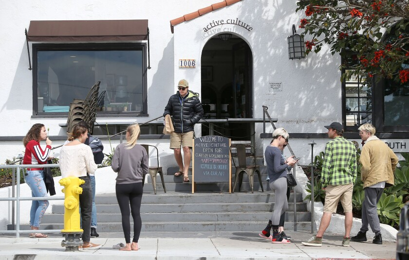 Small groups wait on the sidewalk for phone-in pickup orders at Active Culture in Laguna Beach as businesses work to comply with directives to avoid public gatherings and uphold social distancing guidelines during the coronavirus pandemic.