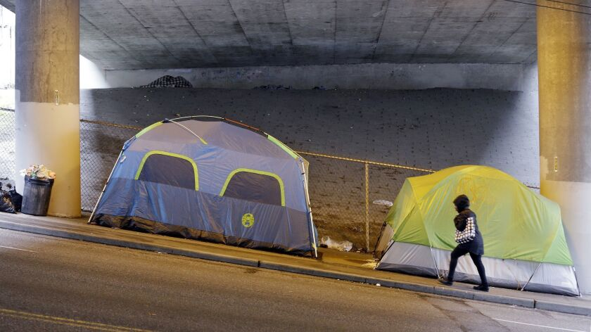 FILE - In this March 8, 2017 file photo, a person walks up a hill next to tents lined up beneath a h