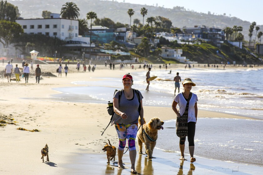 People stroll along the sand in Laguna Beach in May 2020.
