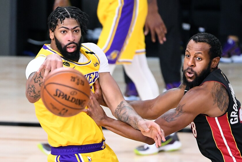 Lakers' Anthony Davis gets a pass off in front of Miami Heat's Andre Iguodala.