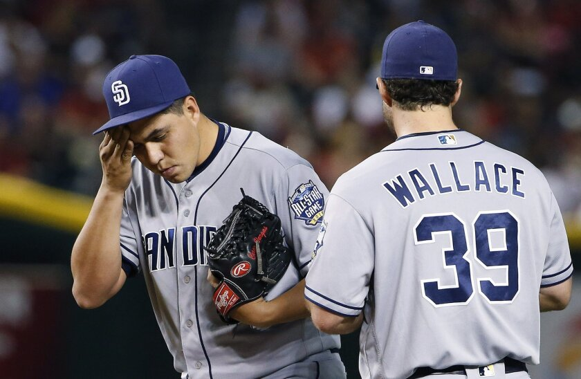 San Diego Padres pitcher Cesar Vargas, left, wipes sweat from his face as he gets a visit from Brett Wallace after giving up three runs to the Arizona Diamondbacks during the second inning of a baseball game Saturday, May 28, 2016, in Phoenix. Vargas was removed later in the inning. (AP Photo/Ross D. Franklin)