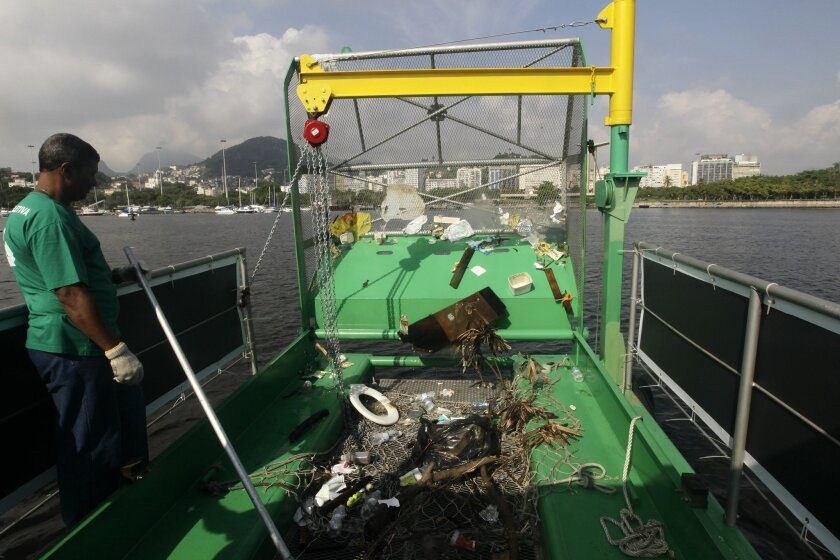 A worker stands next to trash collected by a garbage-collecting barge at the Guanabara Bay, in Rio de Janeiro, Brazil, Monday, Jan. 6, 2014. Levels of fecal coliforms are so high that nearly all the beaches that dot the 148-square-mile (383-square-kilometer) bay have long been abandoned, and some observers have warned of possible heath risks to athletes who come in contact with the water. (AP Photo/Silvia Izquierdo)