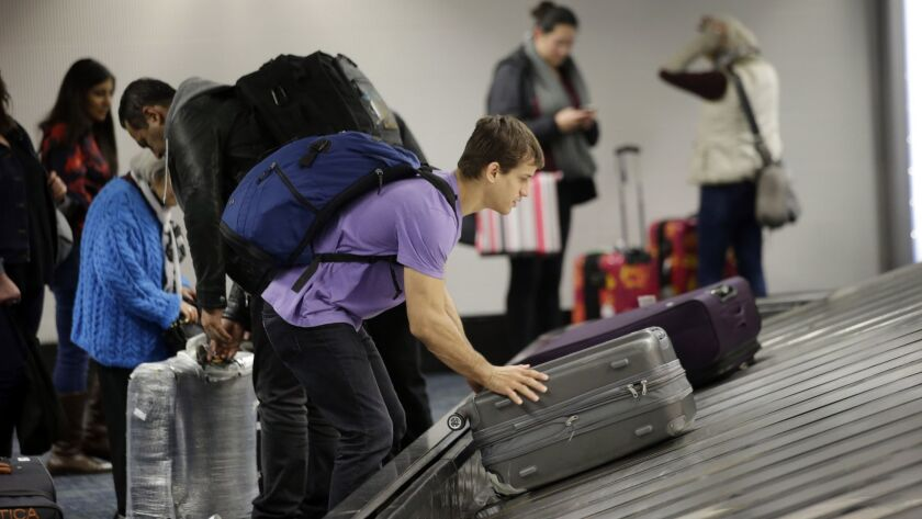 A traveler gathers his luggage at the San Francisco International Airport Sunday, Nov. 22, 2015, in