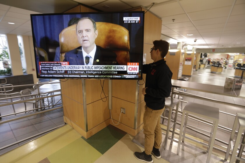 University of Utah student Suyog Shrestha turns on a TV in the student union on the campus in Salt Lake City as Rep. Adam Schiff, the Democratic chairman of the House Intelligence Committee, makes his opening remarks Wednesday, Nov. 13, 2019. The U.S. House launched the first public hearing Wednesday of Donald Trump's impeachment investigation, the extraordinary process to determine whether the 45th president of the United States should be removed from office. (AP Photo/Rick Bowmer)