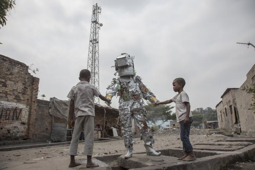 "Street artist Kongo Astronaut greets children in the documentary ""System K."""