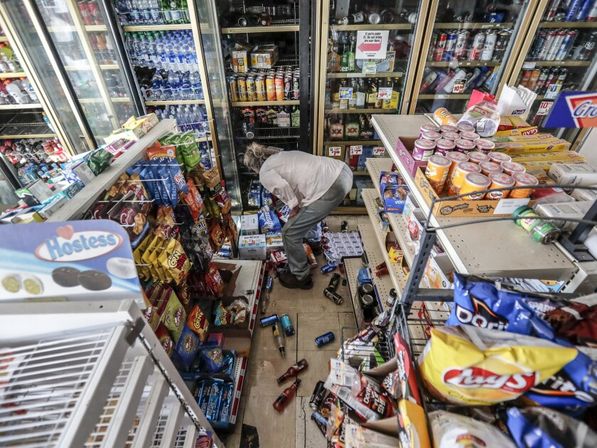 A customer rummages through the rubble at the severely damaged Shell food mart in Trona, Calif., less than a day after the Ridgecrest earthquake in July.