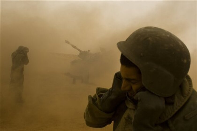 """In this Dec. 29, 2010 photo, Israeli soldiers cover their ears as a shell is fired during an army drill near the Shivta Field Artillery School, southern Israel. Israel is among several nations to harness digital and satellite technology to develop """"C4I"""" systems _ short for """"command, control, communications, computers and intelligence."""" The latest version of the communication system that compiles battlefield information in an easy-to-use, video game-like interface, allows all forces on the ground to communicate instantaneously.(AP Photos/Bernat Armangue)"""