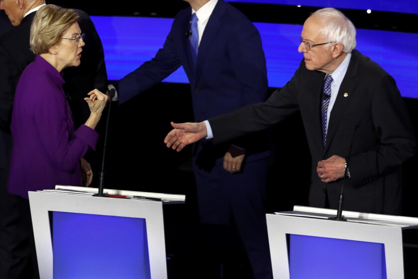 Democratic presidential candidate Sen. Elizabeth Warren and Sen. Bernie Sanders talk Tuesday after a Democratic presidential primary debate hosted by CNN and the Des Moines Register in Des Moines.