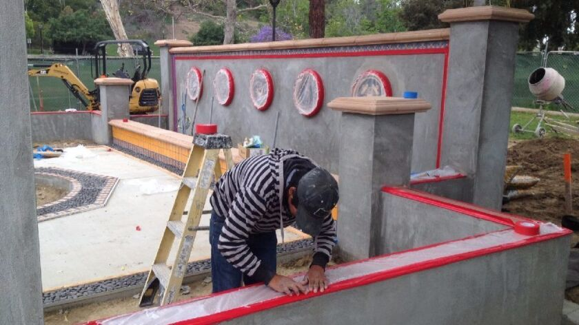 Victor Ramirez works on a wall at the veterans memorial in May at La Colonia Park in Solana Beach, where the city also plans to build a skatepark next year.