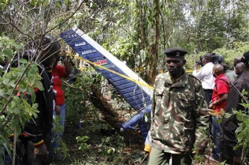 Kenyan officials inspect the area of the helicopter wreckage after it crashed in Ngong forest, on the outskirts of Nairobi, Kenya, Sunday, June 10, 2012. Kenyan police say Sunday June 10, 2012, cabinet minister George Saitoti, who once served as Kenya's vice president, was one of seven people kille