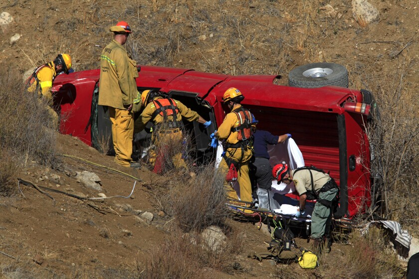 Firefighters remove the dead and injured from a truck that plunged 200 feet down an embankment early Friday in Santa Clarita.