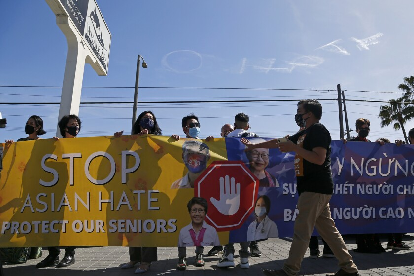 """Members of a group hold a banner as an airplane skywrites """"No Hate."""""""