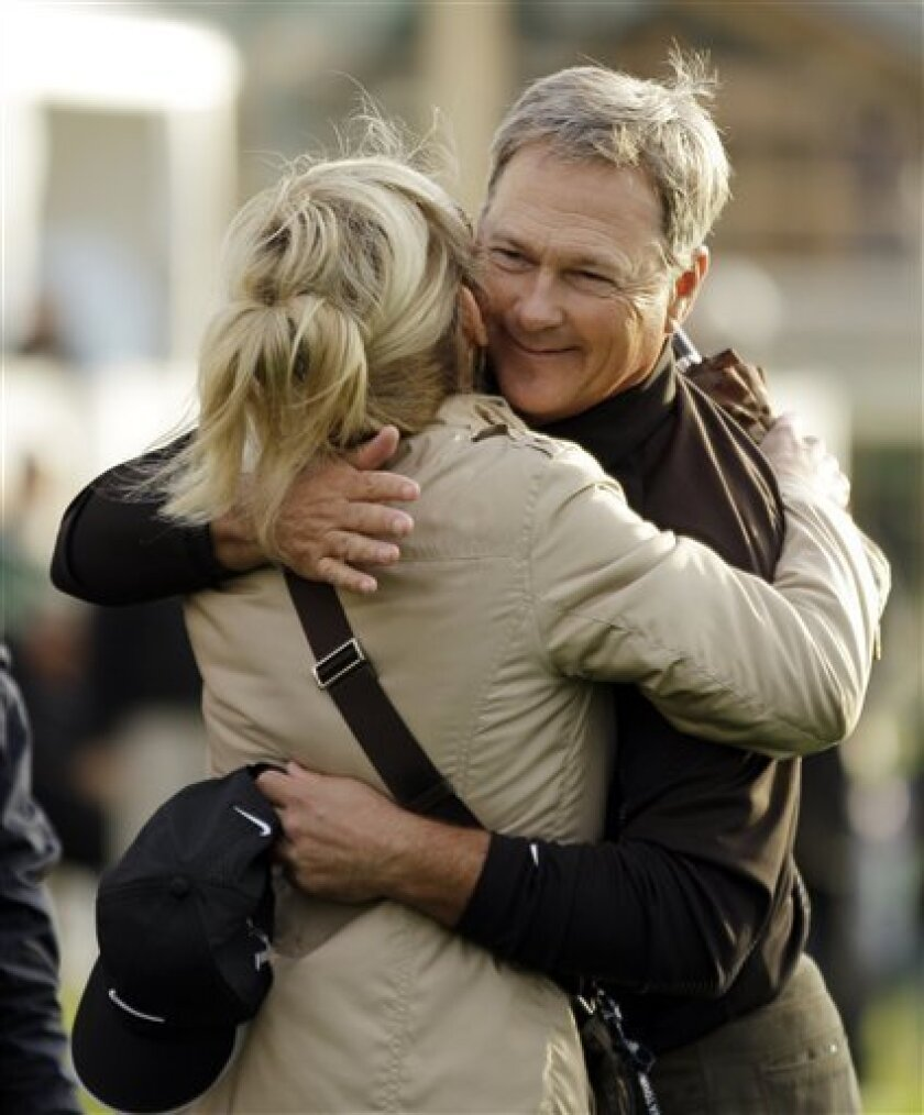 John Cook hugs his wife Jan after winning the Charles Schwab Cup Championship golf tournament in San Francisco, Sunday, Nov. 7, 2010. Cook won the tournament by two strokes after shooting a 4-under-par 67 to finish at total 17-under-par. (AP Photo/Eric Risberg)