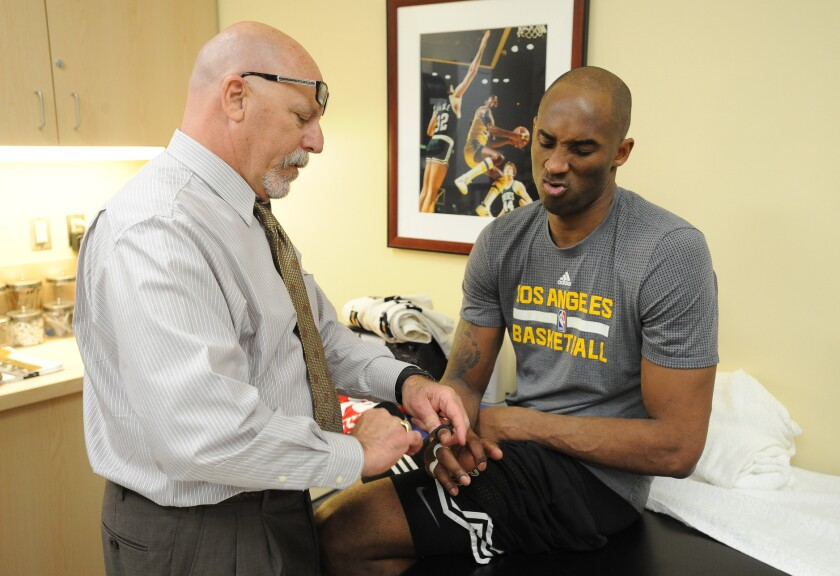 Then-Lakers trainer Gary Vitti tapes one of Kobe Bryant's fingers Feb. 19, 2016, at Staples Center.