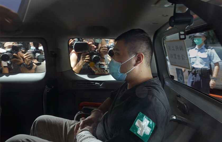 FILE - In this July 6, 2020, file photo, Tong Ying-kit arrives at a court in a police van in Hong Kong. A lawyer for Tong, who convicted under Hong Kong's national security law, asked Thursday, July 29, 2021, for no more than 10 years in prison instead of the possible life sentence faced by the former restaurant waiter in a closely watched case as China tries to crush a pro-democracy movement. (AP Photo/Vincent Yu, File)